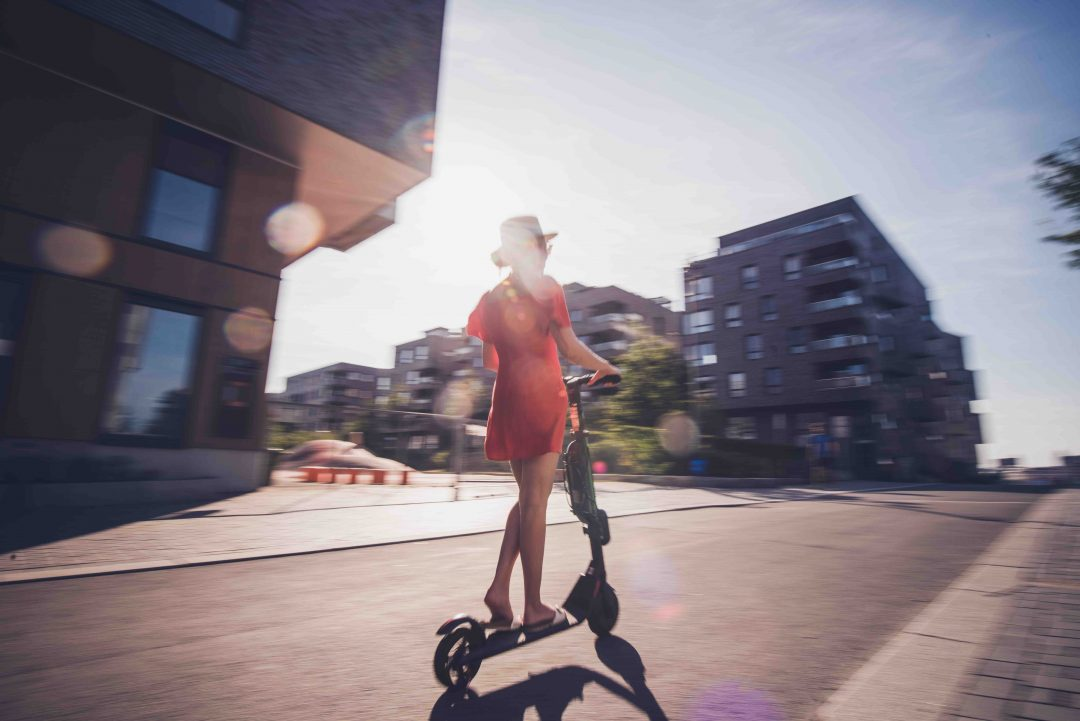 Rear view of female on electric scooter.