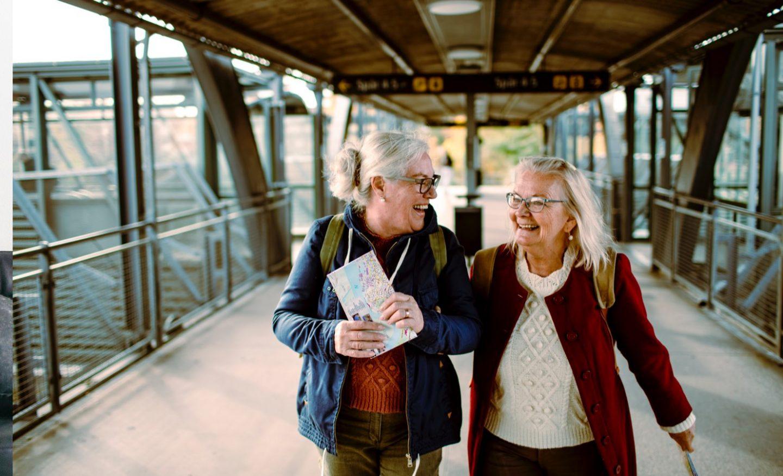 Två kvinnor på som ler och går bredvid varandra