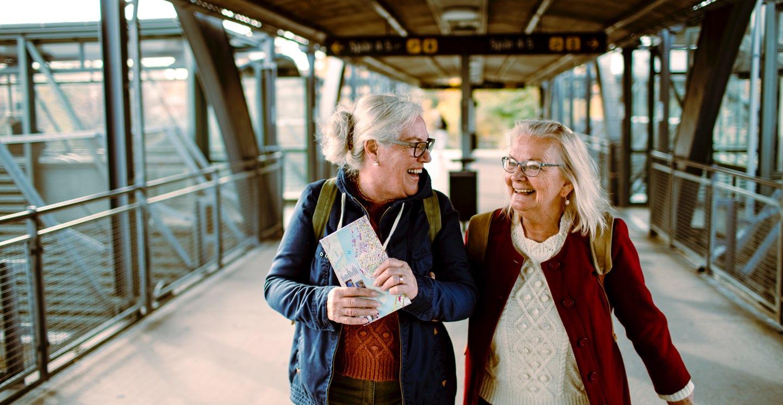 Två kvinnor som ler och går bredvid varandra